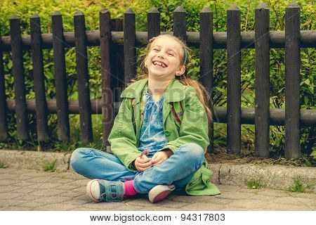 Little laughing schoolgirl  sitting on the street with her backpack