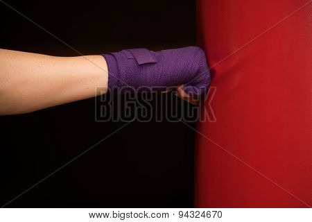 Woman hitting boxing bag, side view