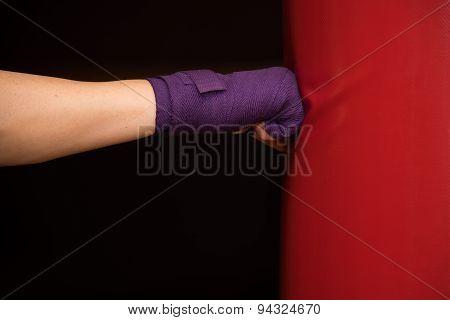 Woman hitting boxing bag, side view