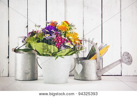 Still-life with flower bouquet in tin bucket, watering can, old milk canister, grunge processing