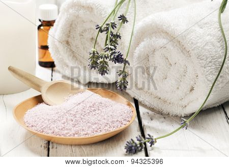 Wooden bowl of bath mineral with flowers, towels, candle and aromatic essence