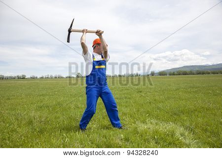 Worker With Pickaxe On A Green Meadow