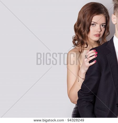 beautiful lovely girl in a black dress standing over his shoulder his beloved boyfriend in a black s