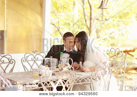Bride And Groom Sitting On Table
