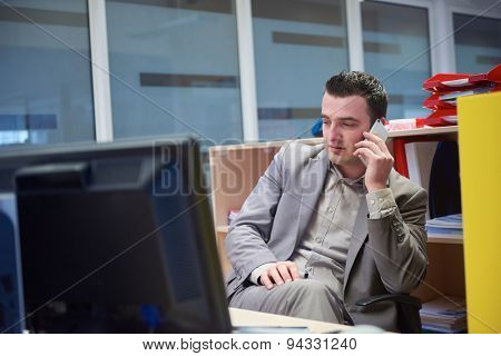 young business man working on computer and talking by phone on modern office indoors