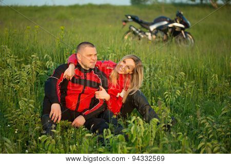 biker girl and man sitting on the grass near a motorcycle