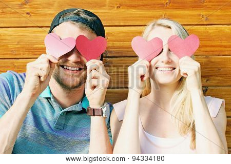 Fall In Love Concept - Young Couple Holding Paper Hearts Over Eyes
