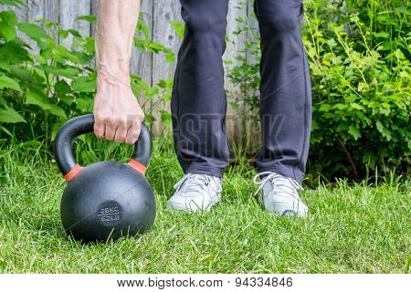 outdoor fitness concept - weight training with a heavy iron competition kettlebell (62lb/28 kg) on green grass in backyard