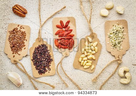 a variety of superfood (nuts, berries, grain, seed) on paper price tags against grunge barn wood background
