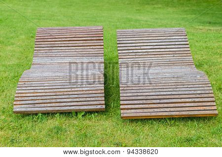 Two Wooden Lounge Sunbeds Standing On Green Grass In Park