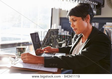 Female restaurant manager working at counter