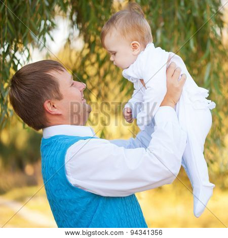 Dad And Baby Playing Together Outdoors