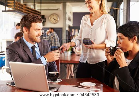 Two business people with laptop paying in a coffee shop
