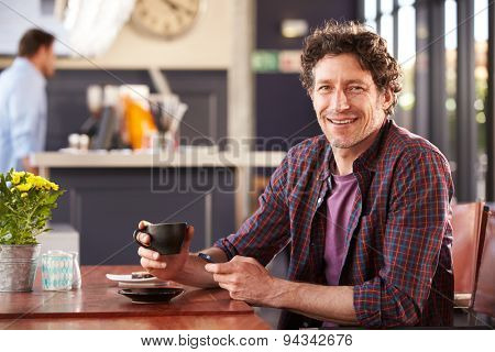 Man at coffee shop using phone, portrait