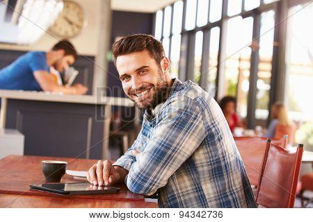 Man using digital tablet in a coffee shop, portrait