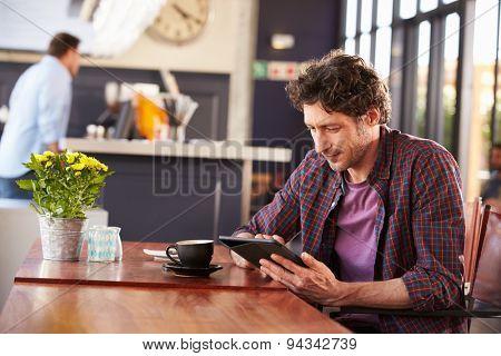 Man at coffee shop, using digital tablet