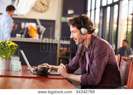 Man working on computer at coffee shop