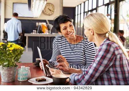 Two women using laptop computer in a coffee shop