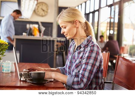 Woman working on laptop computer at a coffee shop