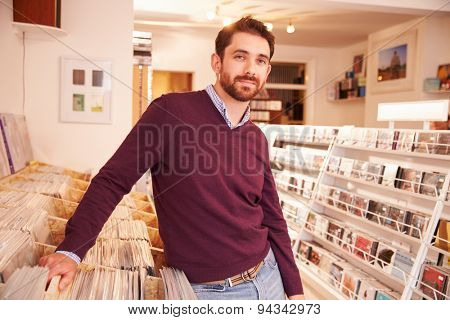Shop owner posing in a record shop