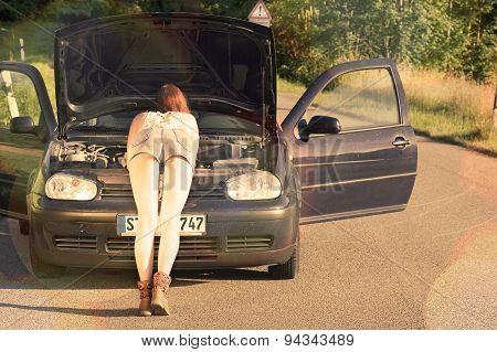 Sexy young redhead woman repairing a broken car