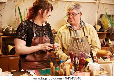 Senior shoemaker training apprentice to work with leather
