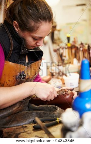 Young shoemaker working with leather in a workshop