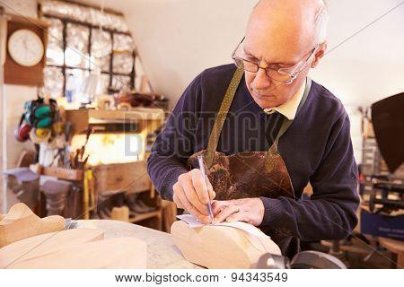Senior shoemaker working in a workshop