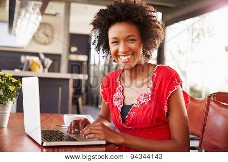 Woman using a laptop at a coffee shop, portrait