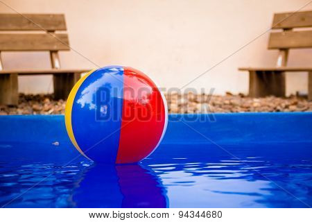Colorful beach ball floating in pool
