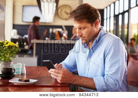 Man using smart phone in a coffee shop