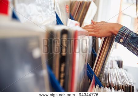 Detail of hands browsing records at a record shop