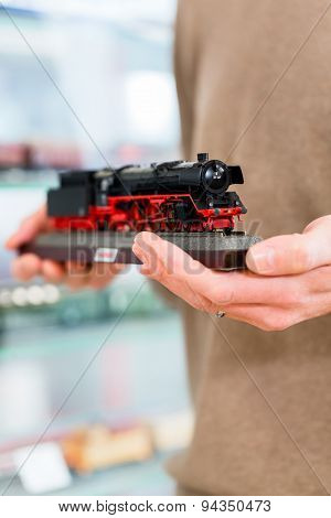 man buying model railroad in toy store holding the model in his hands, close-up