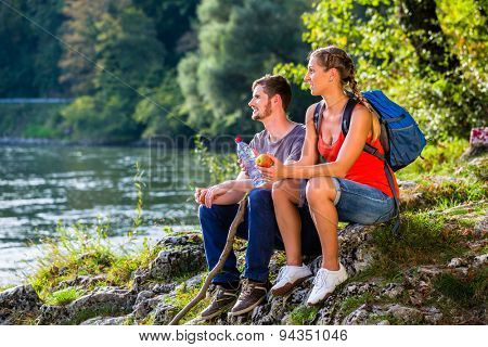 Man and woman having break hiking at river