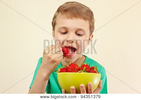 Young boy eating fresh strawberries from bowl