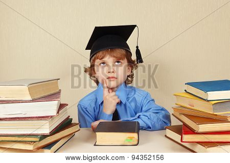 Little serious boy in academic hat among old books