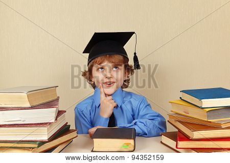Little pensive boy in academic hat among old books