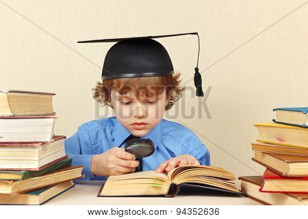 Little serious boy in academic hat studies an old books with magnifying glass