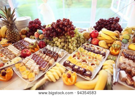 Table Full Of Fruits And Small Cakes