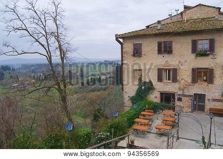 Exterior of the medieval building with a restaurant in early spring in San Gimignano, Italy.