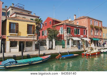View to the channel boats buildings and people at the street in early spring in Murano, Italy.