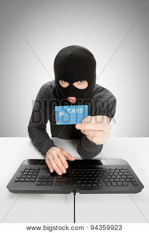 Cybercrime Concept - Hacker In Mask Holding Credit Card