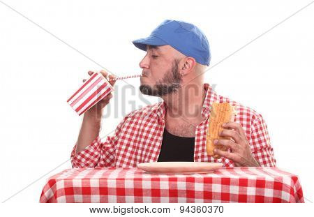 Man is drinking soft drink and eating sandwich