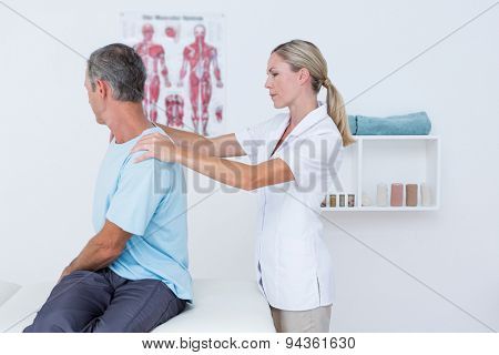 Doctor examining her patient neck in medical office