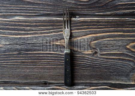 Vintage fork on rustic wooden background