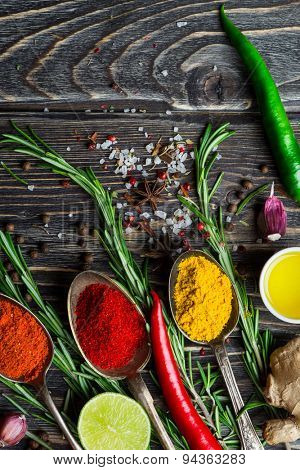 Spices. Herbs and spices selection in old metal spoons over wooden background. Rosemary, salt and chili pepper.