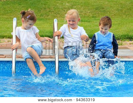 Three little friends have a fun in swimming pool. Happy holidays concept.