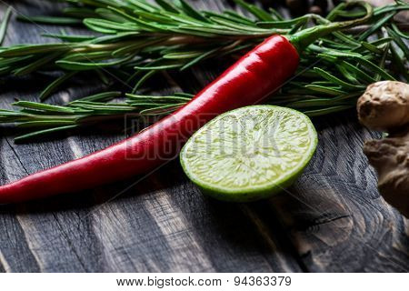 Spices. Chili pepper, lime and rosemary over wooden background.