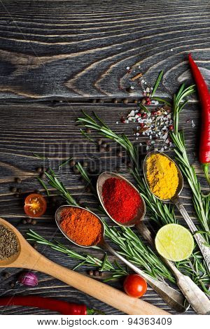Spices. Herbs and spices selection in old metal spoons over wooden background. Rosemary, lime and chili pepper.