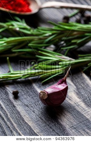 Spices. Garlic, pepper and rosemary over wooden background.